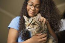 Ragazza con il gatto dell'animale domestico sulle ginocchia — Foto stock