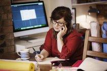 Mujer usando smartphone y tomando notas con lápiz - foto de stock