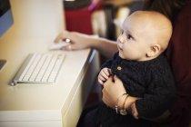 Baby sitzt auf Erwachsene Knie — Stockfoto
