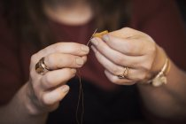 Woman using needle — Stock Photo