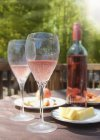 Wine glasses with bottle on table — Stock Photo