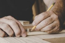 Man marking piece of wood with pencil — Stock Photo