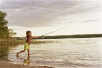 Girl standing in lake fishing with rod — Stock Photo
