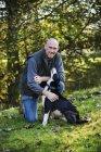 Farmer patting his sheepdog — Stock Photo