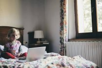 Girl sitting on bed in hotel room — Stock Photo