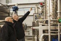 Zwei Männer überprüfen einen Metalltank — Stockfoto