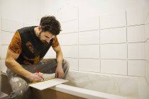 Builder, tiler working in a bathroom — Stock Photo
