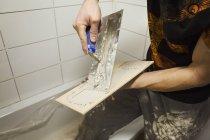 Tiler spreading adhesive on a tile. — Stock Photo