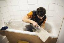 Builder, tiler sitting in a bathtub — Stock Photo