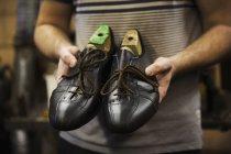 Homem segurando par de sapatos — Fotografia de Stock