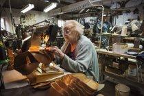Mulher mais velha na oficina do sapateiro . — Fotografia de Stock