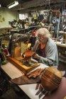 Mulher mais velha na oficina de um sapateiro . — Fotografia de Stock