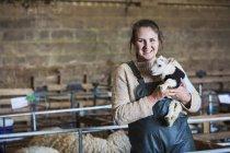 Mulher segurando cordeiro recém-nascido — Fotografia de Stock