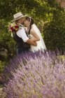 Newlyweds standing outdoors in a garden — Stock Photo