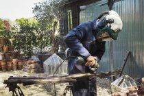 Man working on metal pitchfork — Stock Photo