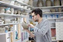 Man inspecting a clay pot — Stock Photo
