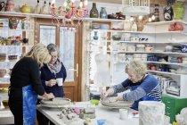 Three women in a pottery studio — Stock Photo