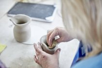 Woman smooth wet clay jug — Stock Photo