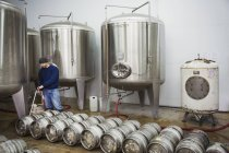 Man filling metal beer kegs — Stock Photo