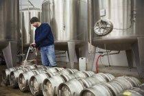 Man filling metal beer kegs — Stock Photo