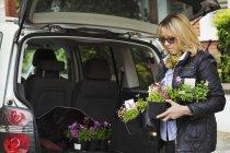 Vasi da fiori in plastica della holding della donna. — Foto stock