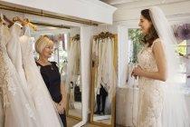 Femme essayer des robes de mariée — Photo de stock