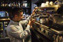Man standing at an espresso machine — Stock Photo