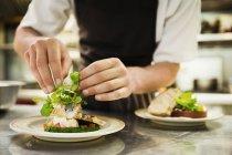 Chef in kitchen adding salad garnish — Stock Photo