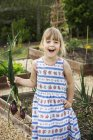 Sorridente ragazza in piedi nel giardino — Foto stock
