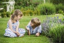 Niña hablando con el hermano en jardín. - foto de stock