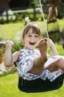 Smiling girl on a swing in a garden. — Stock Photo