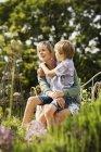 Femme assise dans le jardin avec garçon — Photo de stock
