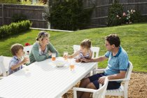Семья, сидя вокруг сада таблицы — стоковое фото