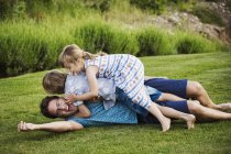 Man lying on grass with children — Stock Photo