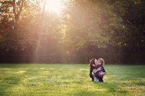 Mujer abrazando y besando a chica joven - foto de stock