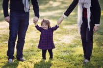 Girl holding hands of man and woman — Stock Photo