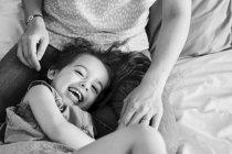 Женщина, сидя на кровати с молодой девушкой — стоковое фото