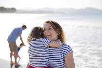 Blonde Frau halten Mädchen am Strand — Stockfoto