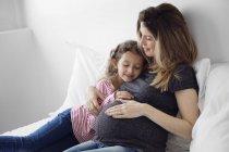 Дівчина і вагітна жінка, сидячи на ліжку — стокове фото