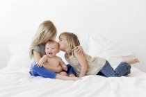 Two blond girls and baby boy on bed — Stock Photo