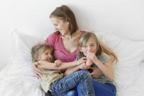 Woman sitting on bed and hugging two girls — Stock Photo