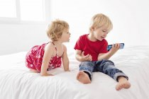 Young boy and girl looking at smartphone — Stock Photo