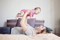 Mother holding aloft baby girl — Stock Photo