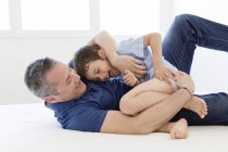 Man and boy play fighting on bed — Stock Photo