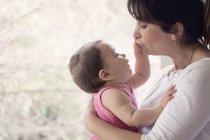 Babymädchen Mütter Gesicht berühren — Stockfoto