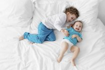 Little boy and baby on bed laughing — Stock Photo
