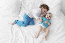 Kleine Jungen und Baby im Bett lachen — Stockfoto