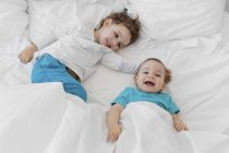Little boys lying on bed laughing — Stock Photo