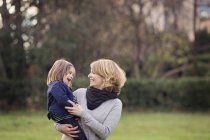 Mother carrying smiling daughter in park — Stock Photo