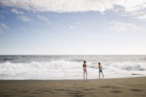 Young boys standing at waters edge — Stock Photo